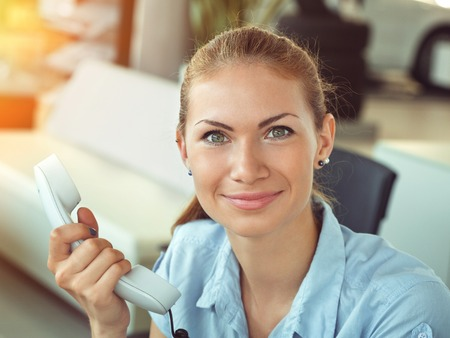 Serious business woman working in office talking on telephone. Idoor shot. Stock Photo