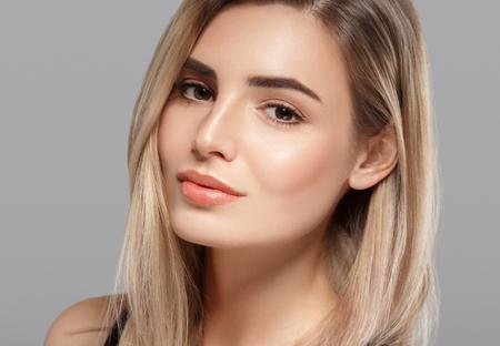 Portrait de belle jeune femme souriante posant attrayant blonde avec des volants de cheveux sur fond gris. Studio tourné Banque d'images - 65881826