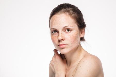 Portrait de visage de femme jeune belle taches de rousseur avec une peau saine. Prise de vue en studio. Isolé sur blanc.
