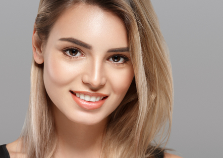 Beautiful young woman portrait smiling posing attractive blond with flying hair on gray background. Studio shot.