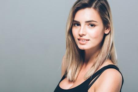 Mooi jong vrouwenportret die stellende aantrekkelijke blond glimlachen. Studio opname.