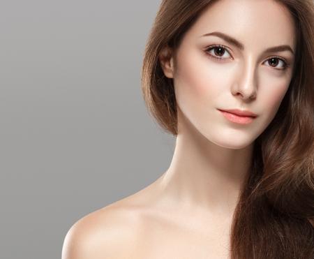 Het jonge mooie portret van het vrouwengezicht met gezonde huid op grijze achtergrond. Studio opname.