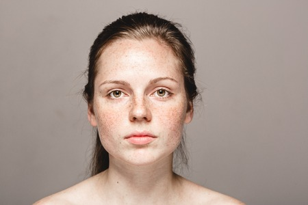 Young beautiful freckles woman face portrait with healthy skin. Studio shot. Isolated on gray.