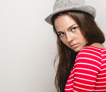Woman portrait in hat hipster in stripes red clothes happy beautiful. Studio shot.