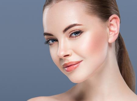 Vrouw schoonheid portret huidverzorging concept op blauwe achtergrond. Studio shot.