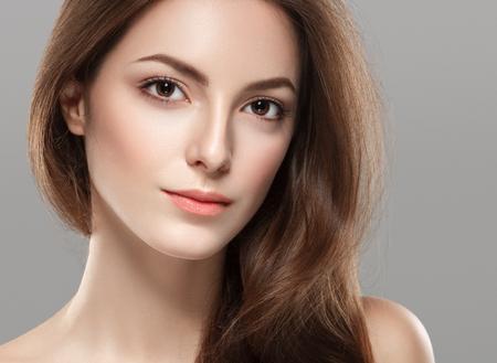 灰色の背景に健康な皮膚の若い美しい女性の顔の肖像画。スタジオ撮影します。