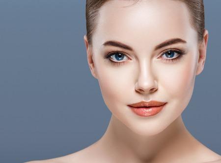 womans hand: Woman beauty portrait skin care concept on blue background. Studio shot. Stock Photo