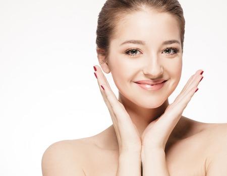 健康な皮膚の若い美しい女性の顔の肖像画。白で隔離。スタジオ撮影します。
