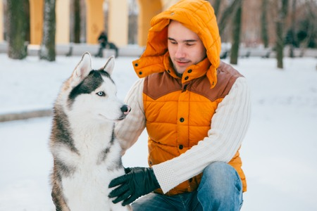 Man walking with dog winter time with snow in forest Huskies friendship. Studio. Stock Photo
