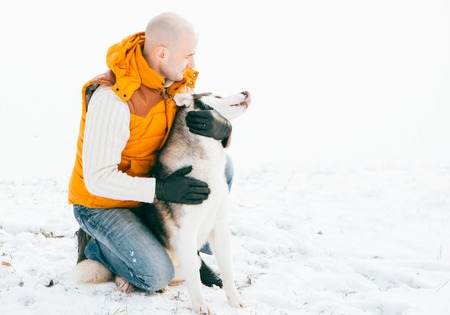 huskies: Man walking with dog winter time with snow in forest Huskies friendship. Outdoor.