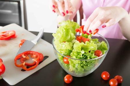 indoor shot: woman mixing a salad in her kitchen. Indoor shot. Stock Photo