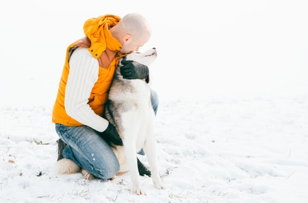 Man walking with dog winter time with snow in forest Huskies friendship. Outdoor.