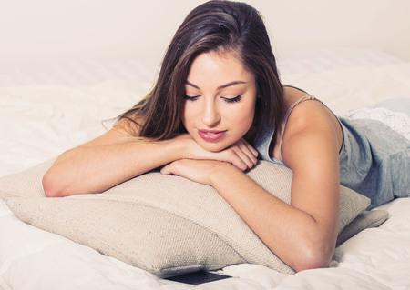indoor shot: Young woman portrait in bedroom on bed alone relaxing looking camera. Indoor shot.