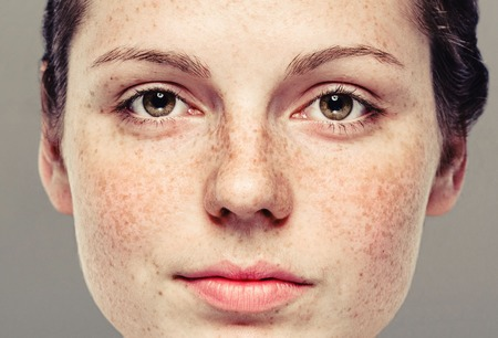 Young beautiful freckles woman face portrait with healthy skin. Gray background. Studio shot. Stok Fotoğraf