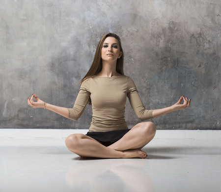 Young woman sitting in lotus position.