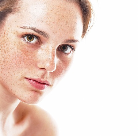 Portrait of smiling young and happy woman with freckles. Isolated on white.