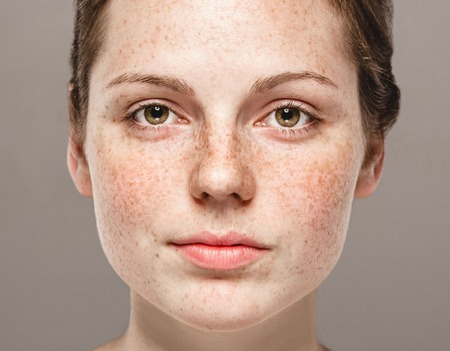 Young beautiful freckles woman face portrait with healthy skin. Gray background. Studio shot. Stock Photo