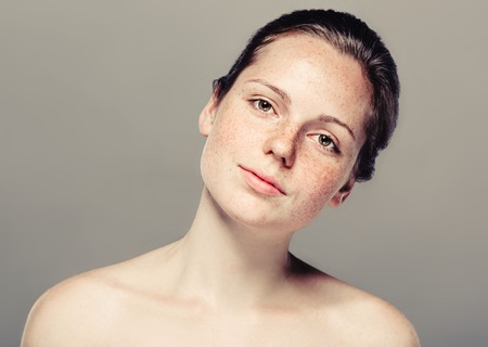 Young beautiful freckles woman face portrait with healthy skin. Фото со стока