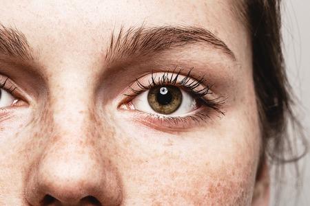A mulher bonita nova das sardas eyes o retrato com pele saudável.