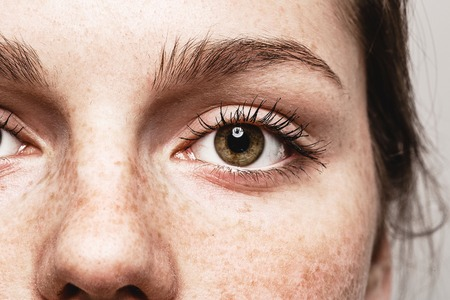 Young beautiful freckles woman eyes portrait with healthy skin. Stock Photo
