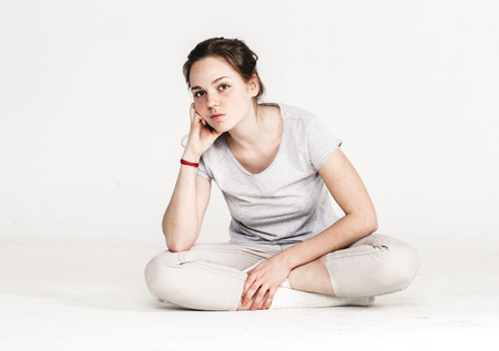 Portrait of a pretty young woman girl sitting on the floor isolated on white. Stock Photo
