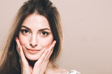 Beautiful young woman touching her cheeks
