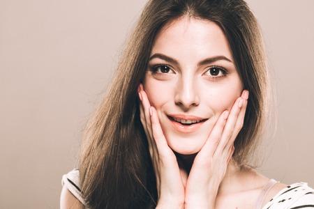 Beautiful young woman portrait touching her cheeks Stock Photo