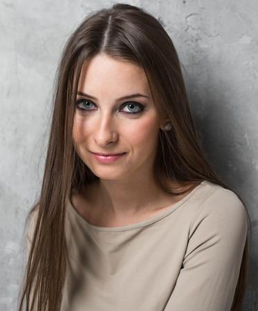 Woman posing near gray background