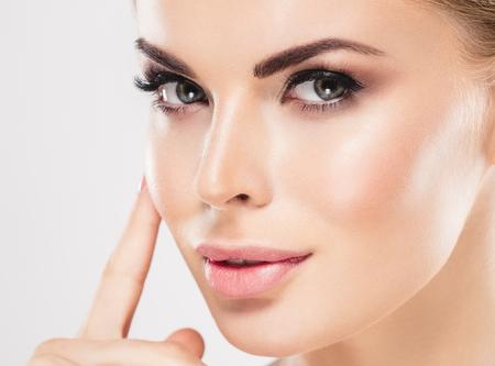 Belleza Mujer cara Retrato Hermosa modelo de Spa Chica con Perfect Fresh Clean Skin. Mujer uñas manicura lápiz labial mismo color pelo rubio Juventud y cuidado de la piel concepto. Aislado en un fondo blanco Foto de archivo