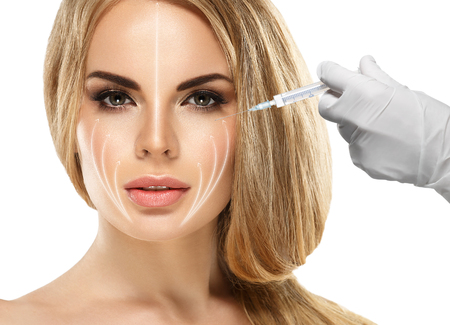 People, Lips, cosmetology, plastic surgery and beauty concept - beautiful young woman face and hand in glove with syringe making injection. Studio shot.