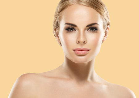 Beauty Woman with perfect healthy skin Portrait. Beautiful Girl smiling Spa model, pampering her skin. Yellow background Stock Photo