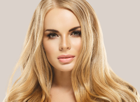 Beauty Woman face Portrait. Beautiful model Girl with Perfect Fresh Clean Skin color lips purple red. Blonde with long hair Youth and Skin Care Concept. Isolated on beige background