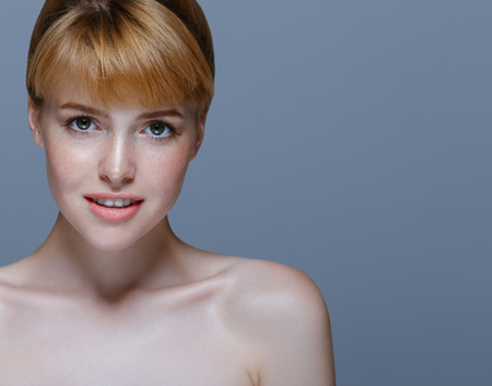 Portrait of a young woman with beautiful red hair freckles skin over gray blue background. Studio shot.