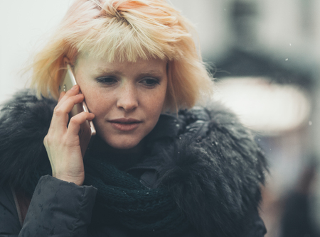 Winter beautiful woman city portrait using mobile. Outdoor shot. Imagens