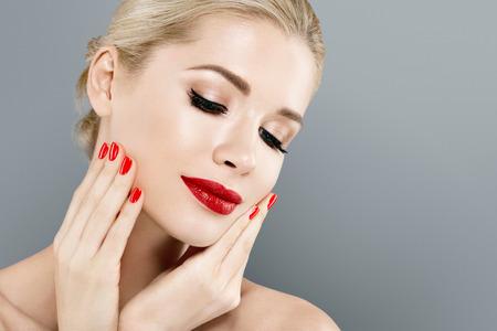 美しい女性金髪の顔の肖像画。美しいスパ モデル完璧な新鮮なきれいな肌を持つ少女。ブロンドの女性は笑みを浮かべてします。若さと肌ケア概念赤い口紅と爪のマニキュア。 写真素材 - 78838858