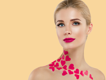 Beautiful woman Valentines Day Hearts concept. Blond Woman red lips over yellow background. Studio shot.