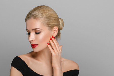 Blond mooi vrouw model over grijze achtergrond. Vrouw nagel manicure lippenstift dezelfde kleur schoonheid portret mooie zorg
