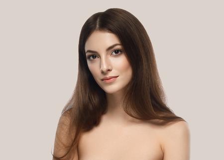 Beautiful woman skincare portrait with hand over beige background. Studio shot. Stock Photo