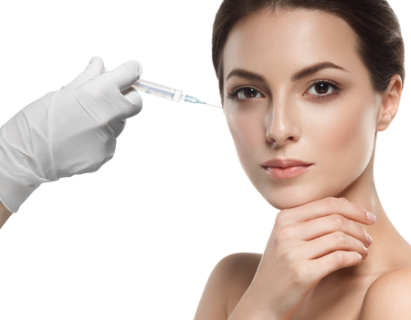People, cosmetology, plastic surgery and beauty concept - beautiful young woman face and hand in glove with syringe making injection