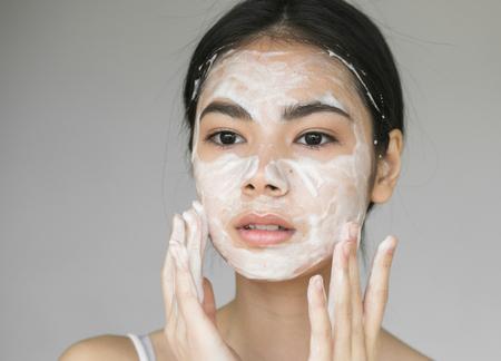 Jeune belle femme se lave le visage avec du savon. Prise de vue en studio.