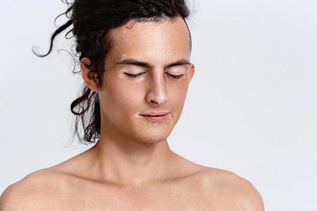 Vitiligo man portrait. Studio shot. Gray background.