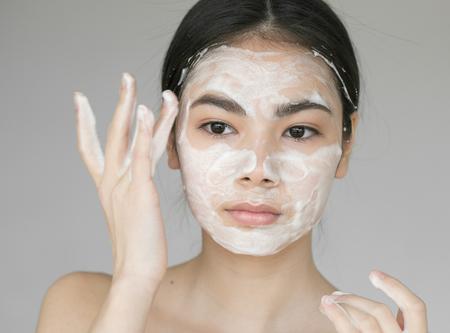 비누로 그녀의 얼굴을 씻는 아름 다운 젊은 여자. 스튜디오 촬영.