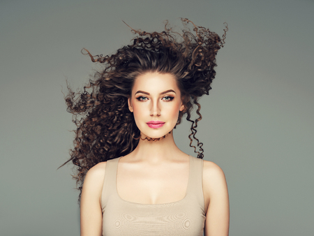 Curly hair woman beautiful beauty portrait, female glamour face with long brunette hairstyle. Studio shot.
