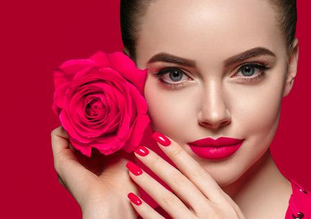 Schönheitsfrau mit dem schönen gelockten Haar und den Lippen der rosafarbenen Blume. Studioaufnahme.