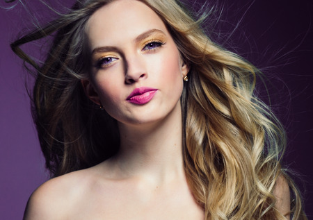Beautiful blonde girl with long curly hair over purple background. Studio shot. 스톡 콘텐츠 - 115481802