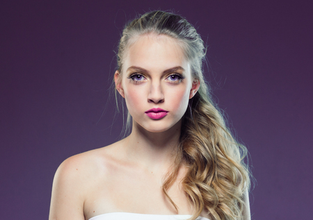 Beautiful blonde girl with long curly hair over purple background. Studio shot. 스톡 콘텐츠 - 115481805