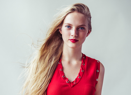 Beautiful long blonde hair woman in red dress natural over white background. Studio shot.