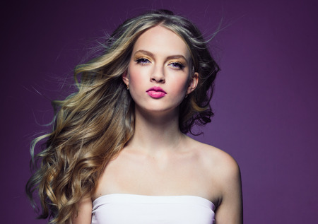Beautiful blonde girl with long curly hair over purple background. Studio shot. 스톡 콘텐츠 - 115528040