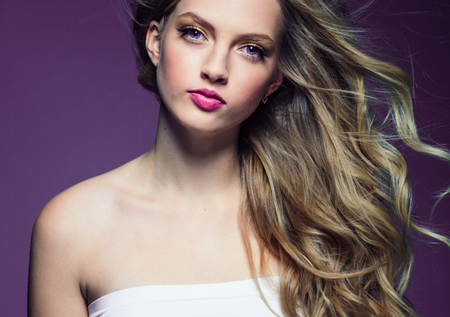 Beautiful blonde girl with long curly hair over purple background. Studio shot.