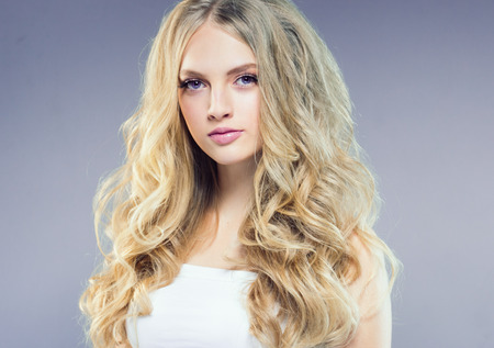 Beautiful blonde girl with long curly hair over purple background. Studio shot. Фото со стока - 115535705